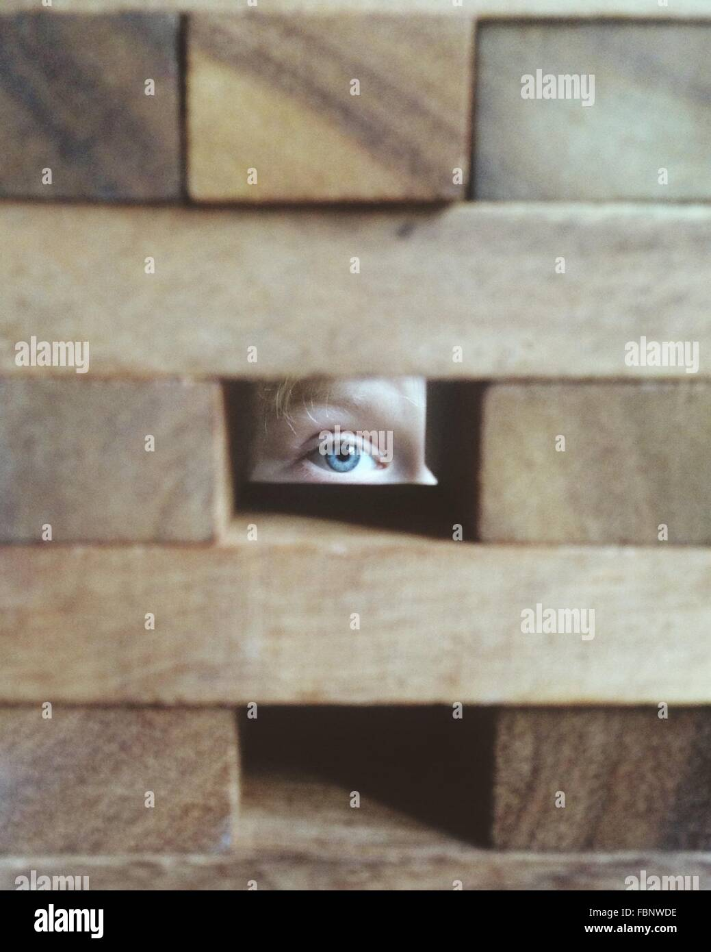 Person Looking Through Block Hole - Stock Image