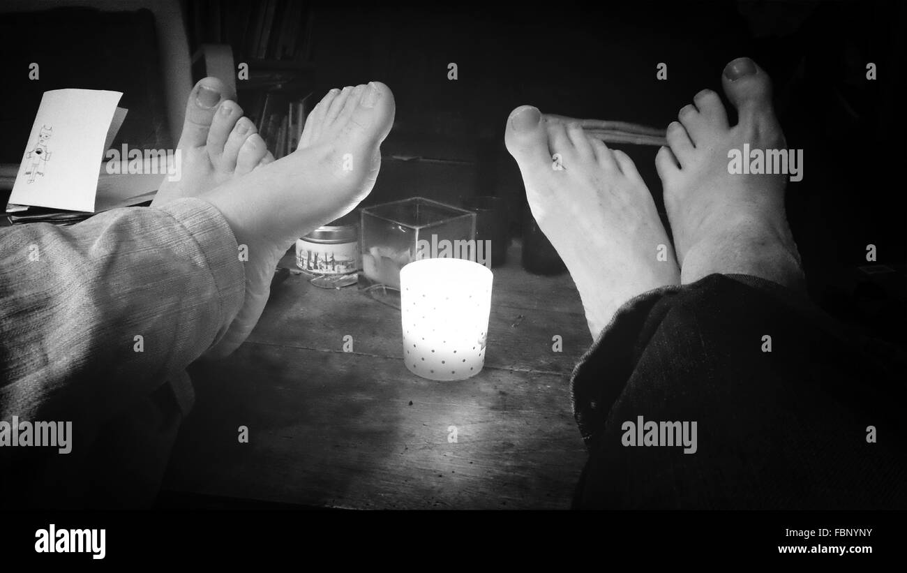 Man Woman With Feet On Candle-Lit Table - Stock Image