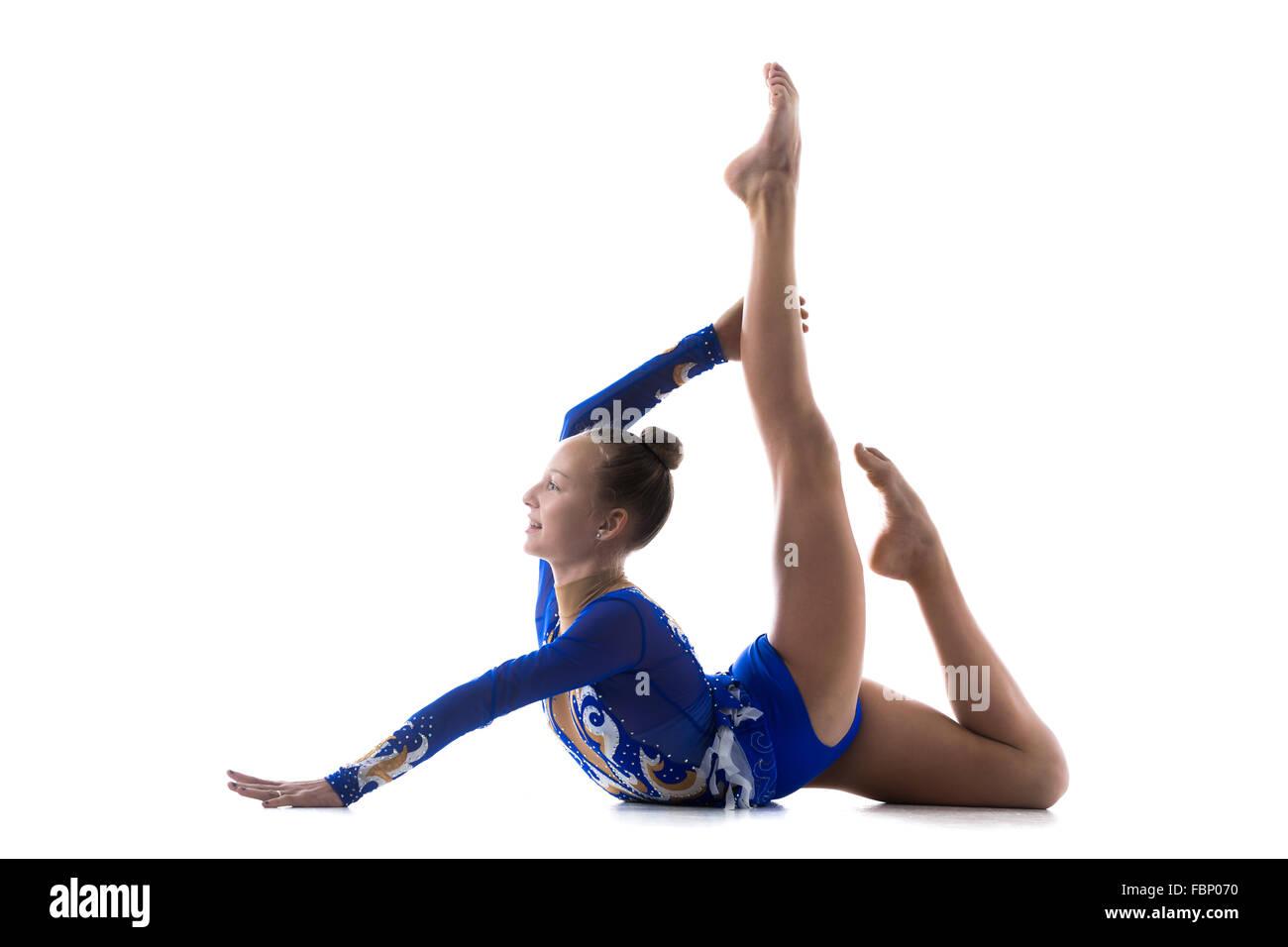 Beautiful smiling gymnast athlete teenage girl wearing dancer blue leotard working out, dancing, posing, doing art - Stock Image