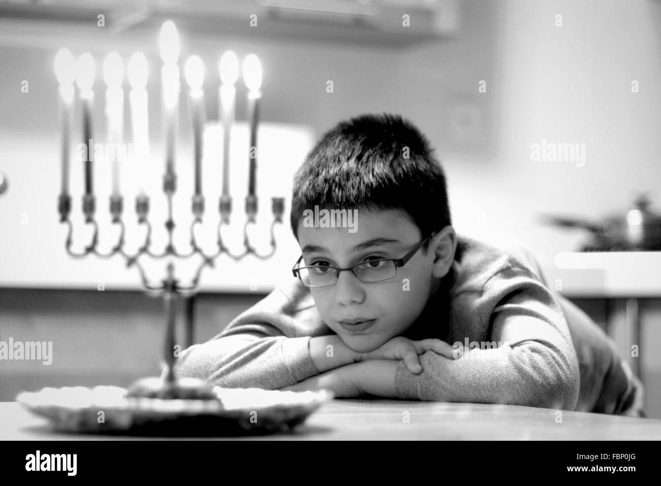 Cute Boy Looking At Lit Candles While Sitting On Table At Home Stock Photo