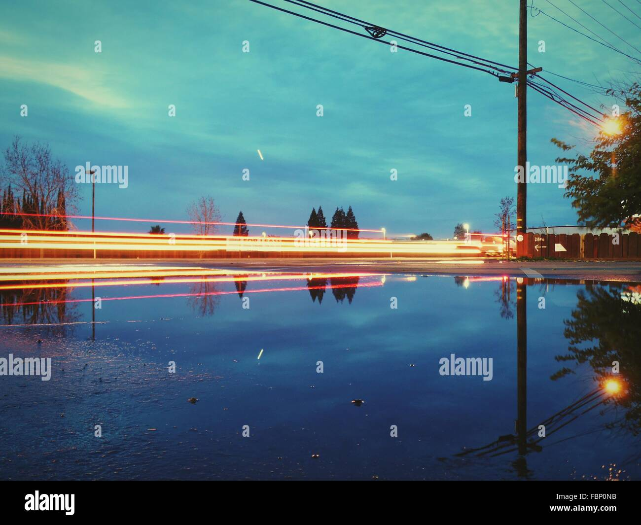 Reflection Of Light Trails And Electricity Pylon In Puddle - Stock Image