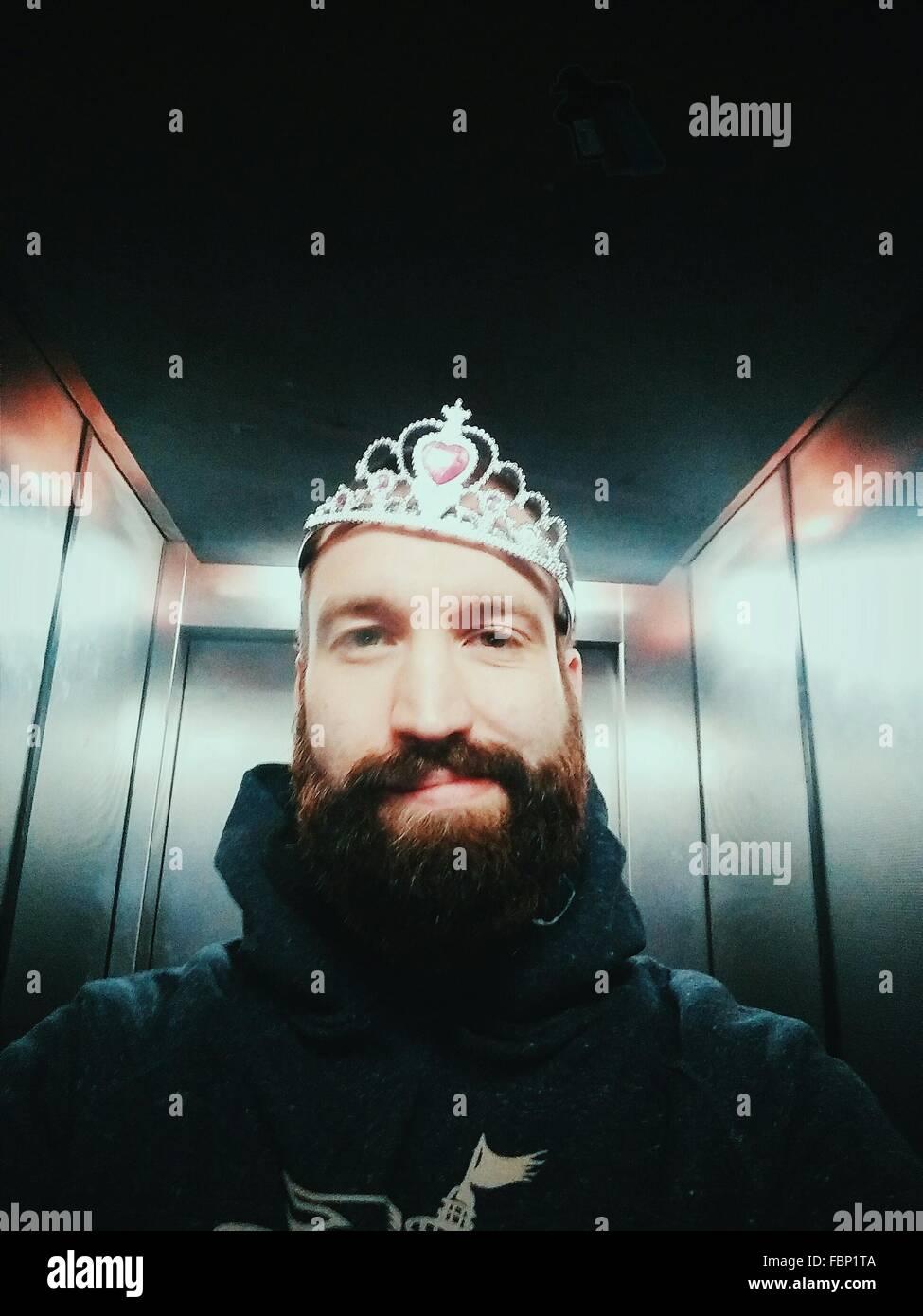 Portrait Of Man Wearing Crown In Elevator - Stock Image