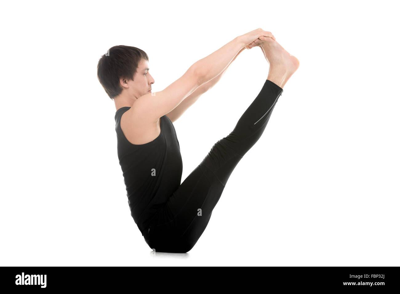 Sporty young man doing yoga or pilates exercises, sitting in Ubhaya Padangusthasana, Both Feet Big Toe, Double toe - Stock Image