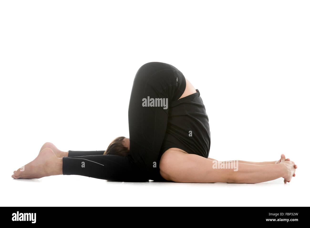 Sporty young man working out, doing yoga or pilates exercises, karnapidasana, ear pressure pose, variation of halasana - Stock Image