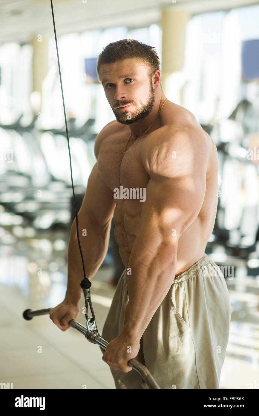 Sportsman doing pull-ups in gym. - Stock Image