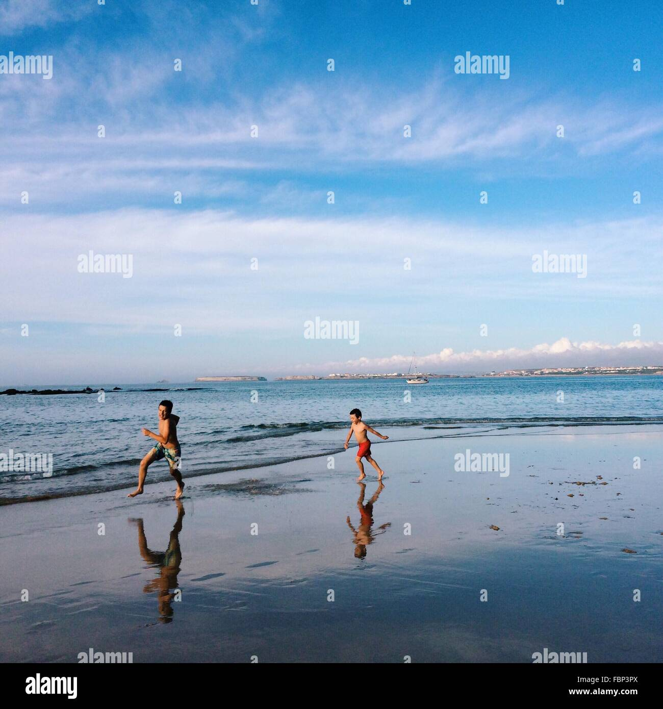 Two Boys Running On Beach - Stock Image