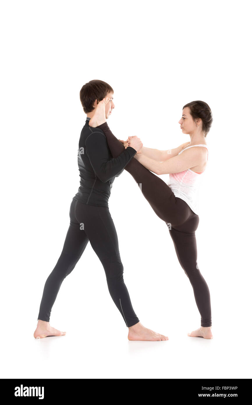 Two sporty people practice yoga in pair, girl doing stretching exercise, Extended Hand to Big Toe yoga pose, Utthita - Stock Image