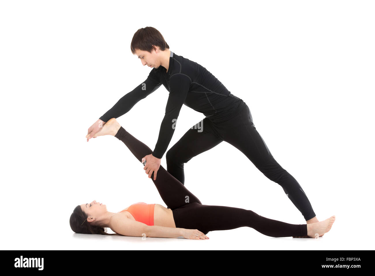 Two sporty people practicing yoga with partner, young male coach helping girl to do reclining hand to big toe pose, - Stock Image