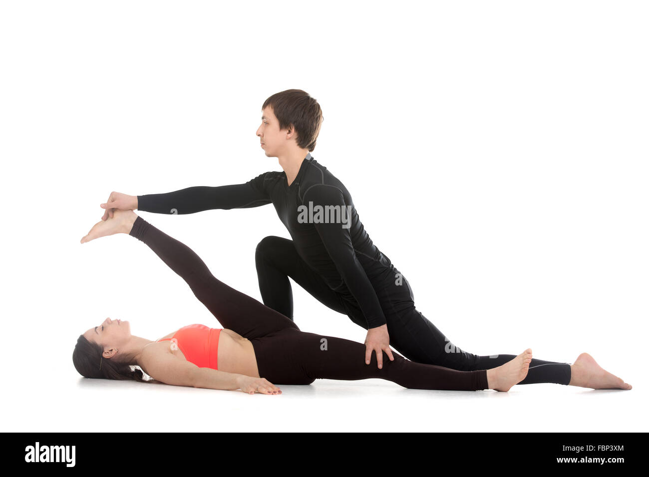 Two sporty people practicing yoga with partner, young man coaching, helping girl to do reclining hand to big toe - Stock Image
