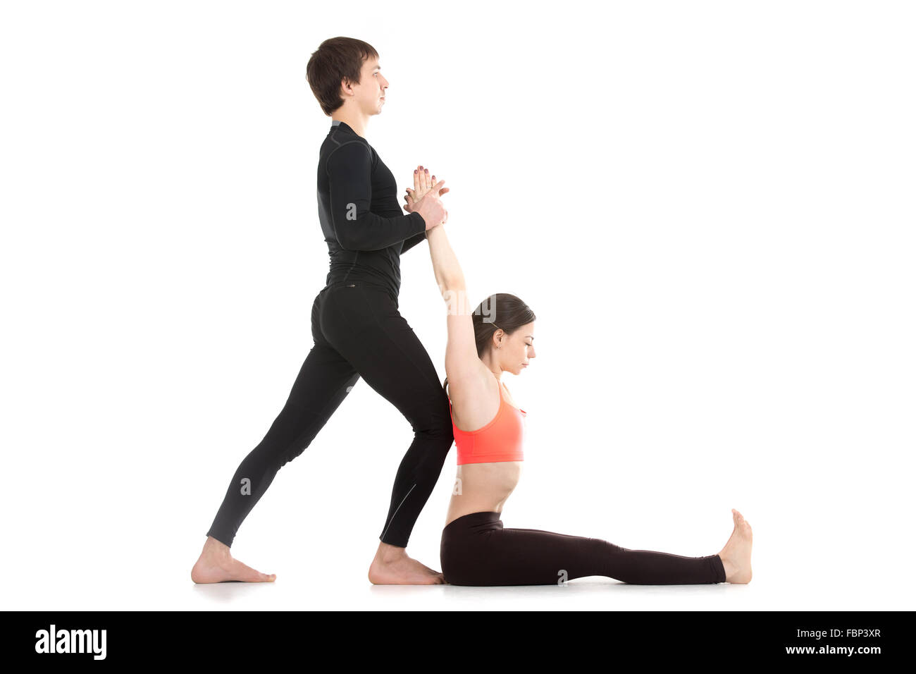 Two sporty people practicing yoga, young man assisting girl doing seated forward bend pose, paschimottanasana, side - Stock Image