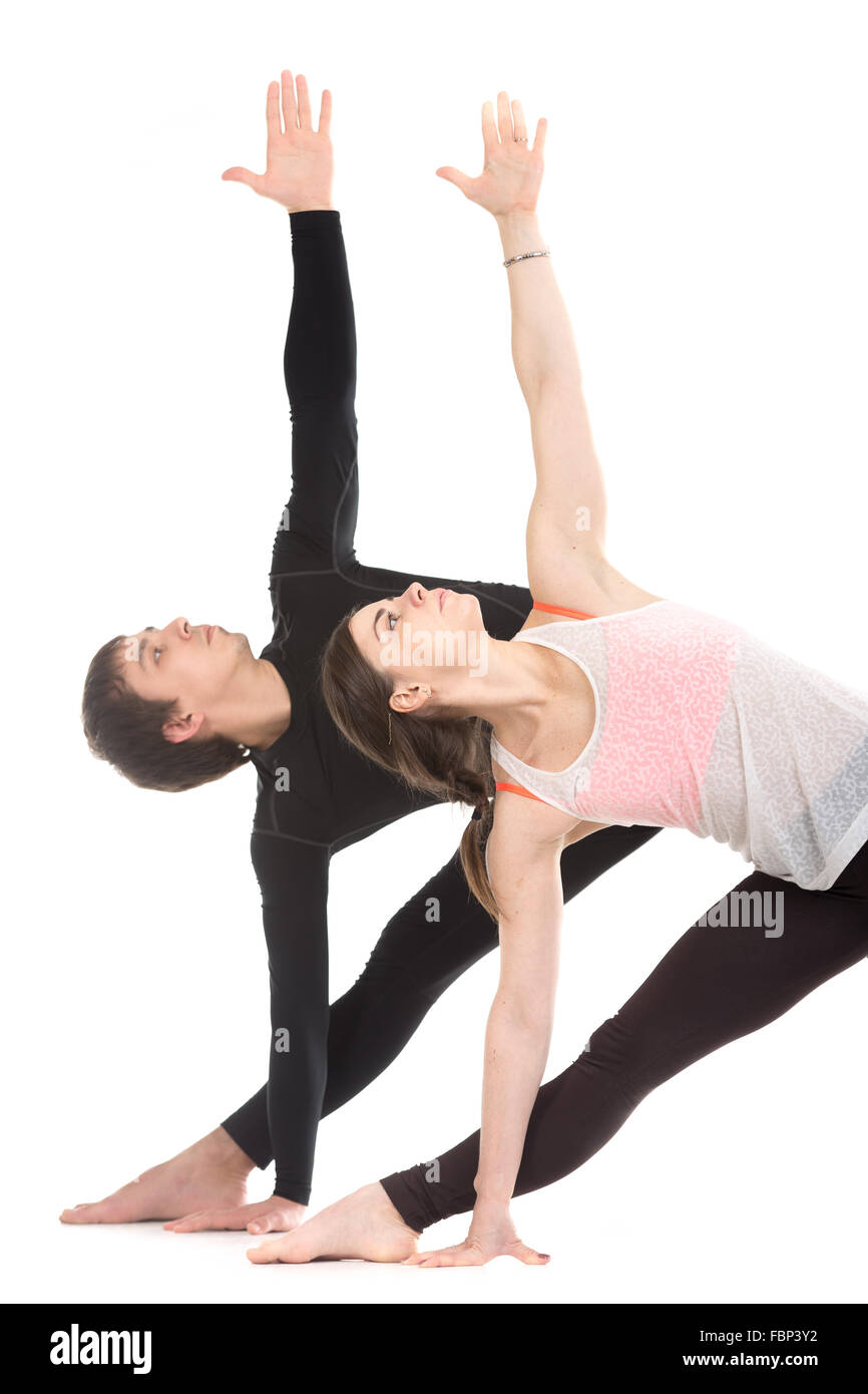 Two sporty people practice yoga with partner, couple doing stretching exercise, extended triangle pose, utthita - Stock Image