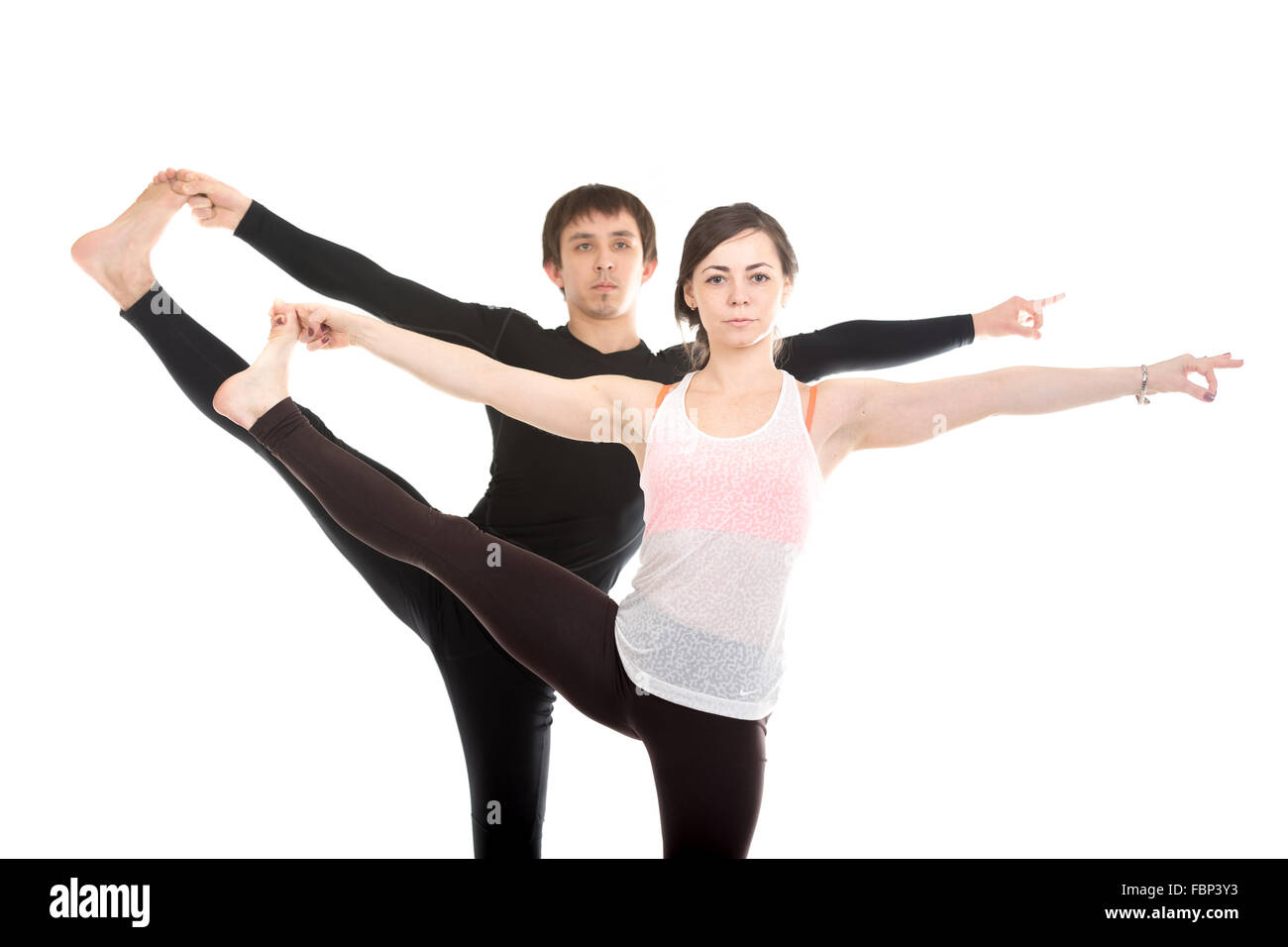 Two sporty people practice yoga with partner, couple doing stretching exercise, Extended Hand to Big Toe yoga pose, - Stock Image