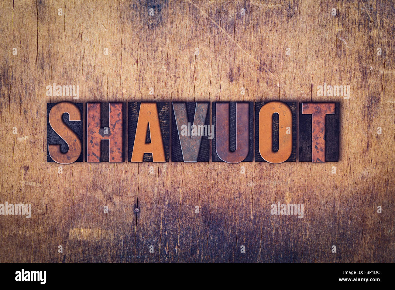 The word 'Shavuot' written in dirty vintage letterpress type on a aged wooden background. - Stock Image