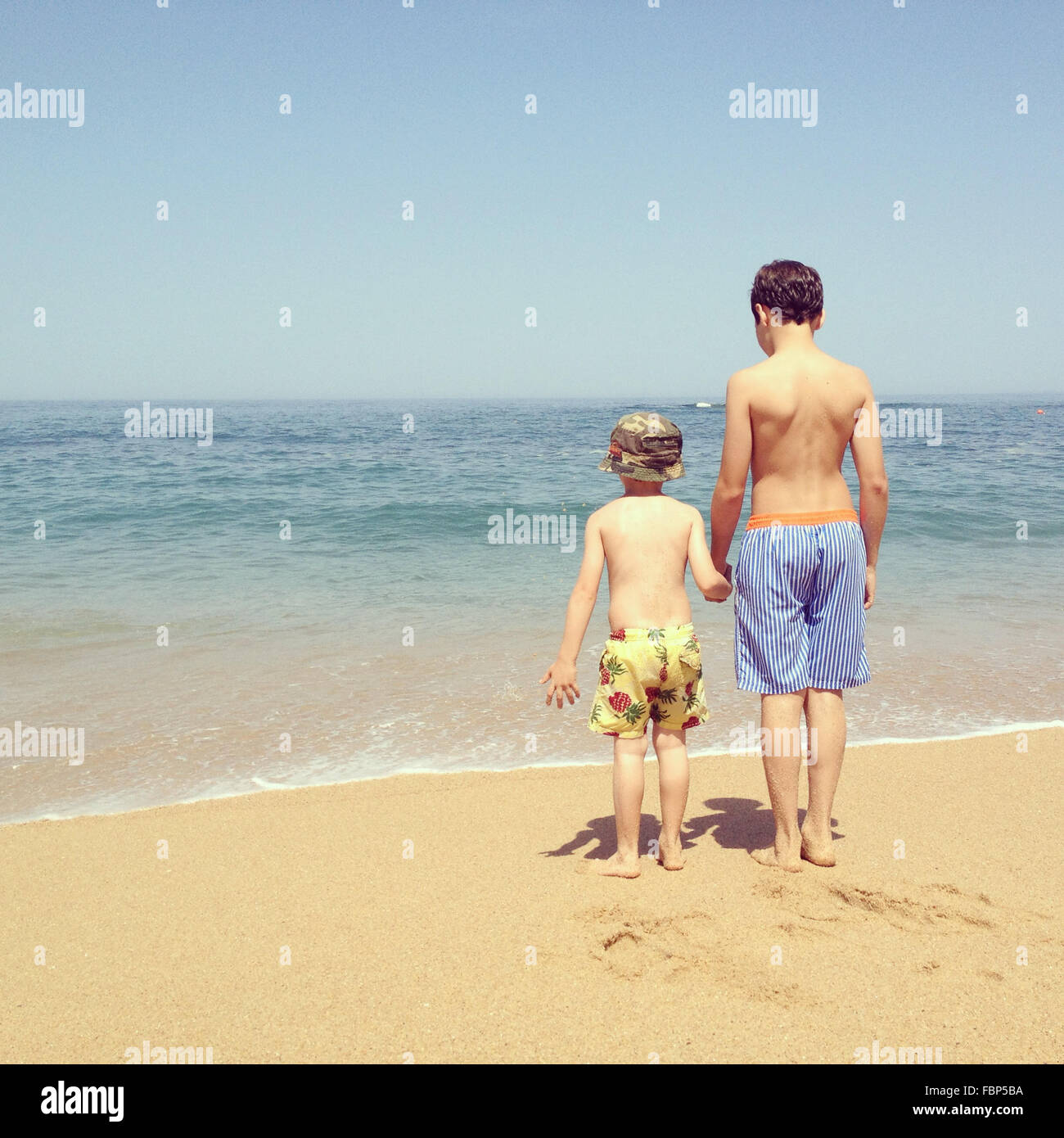 Rear View Of Siblings Holding Hands At Beach - Stock Image
