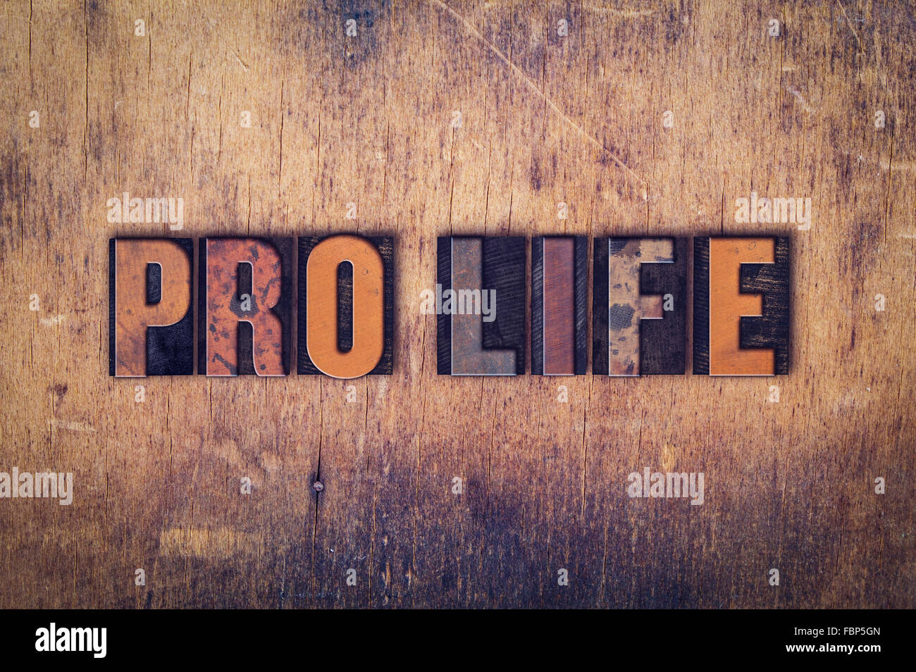 """The word """"Pro Life"""" written in dirty vintage letterpress type on a aged wooden background. Stock Photo"""
