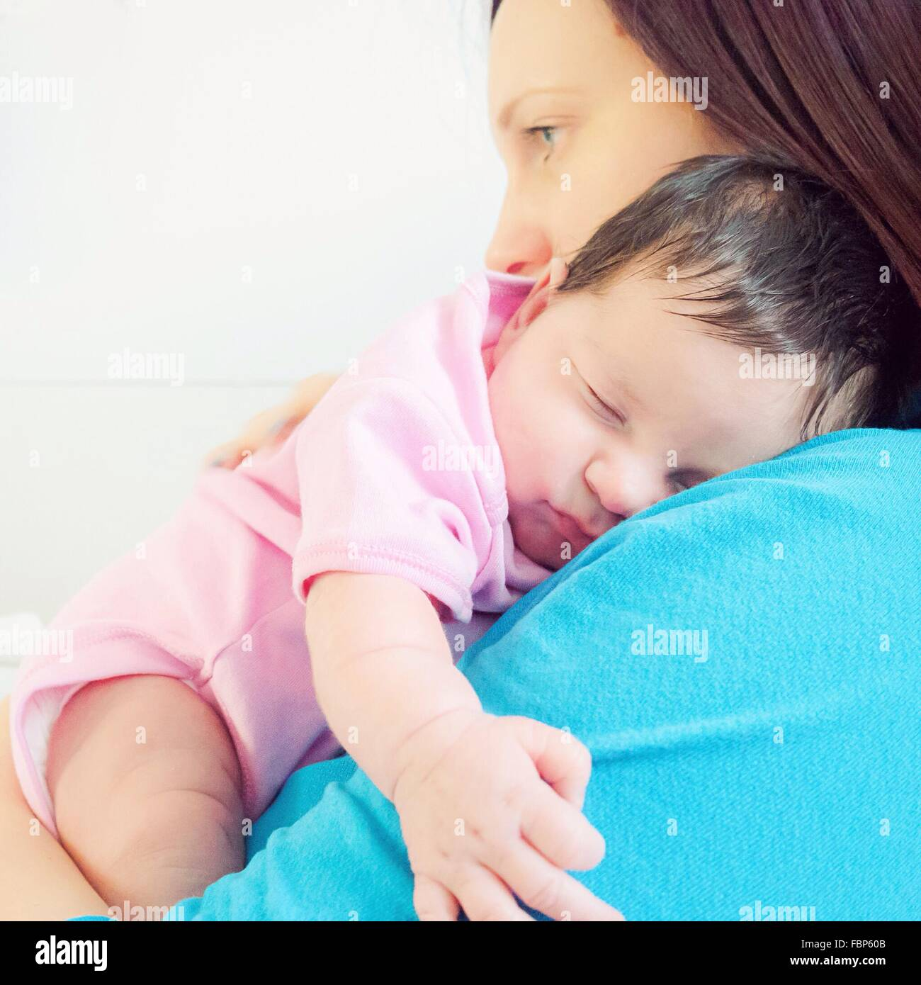 Side View Of Mother Holding Cute Baby Against White Background - Stock Image