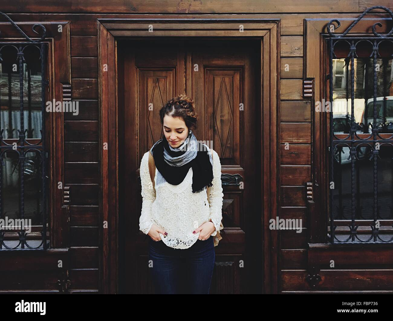 Portrait Of Young Woman In Front Of Wooden Building Stock Photo