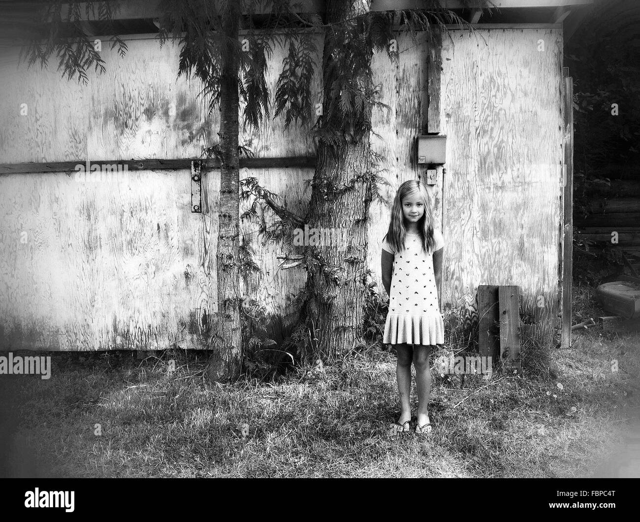 Full Length Portrait Of Girl Standing On Grass Against Wooden Wall - Stock Image
