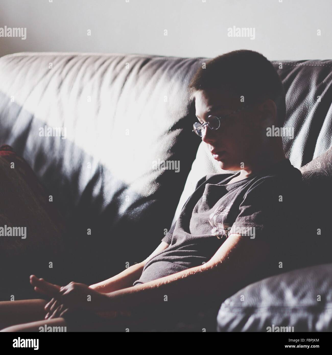 Boy Sitting On Sofa At Home - Stock Image