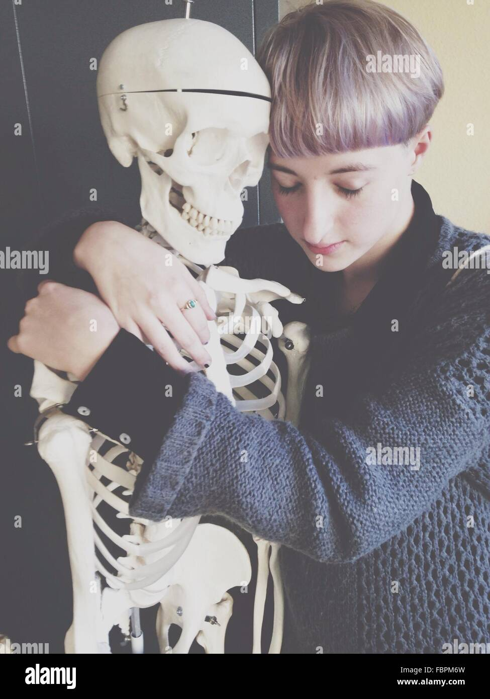 Sad Teenage Boy Hugging Skeleton - Stock Image