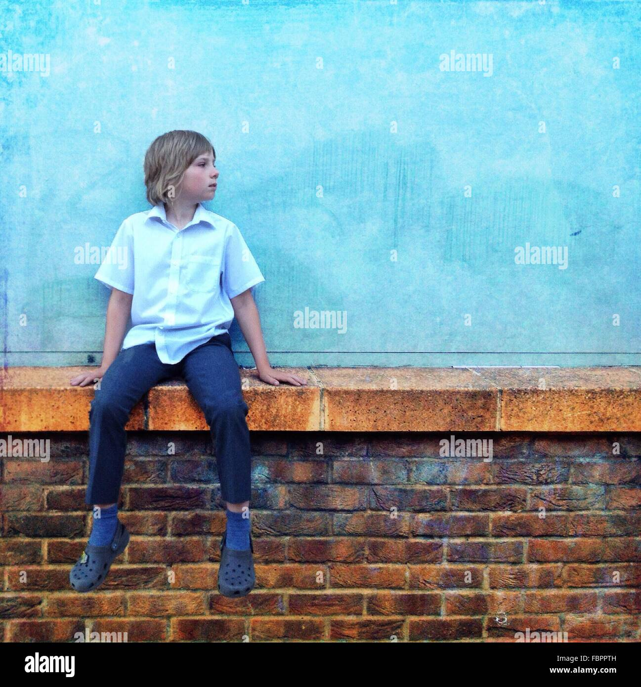Teenage Boy Wearing Blue Shirt And Jeans Sitting On Wall - Stock Image