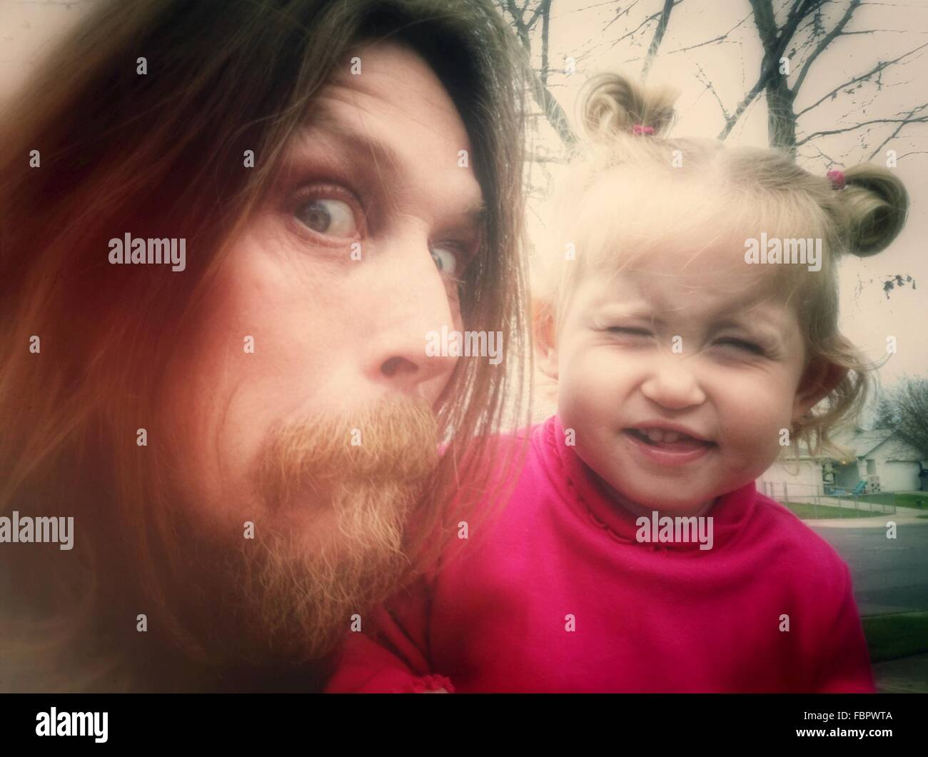 Close-Up Portrait Of A Man And Baby Girl Making Faces Stock Photo