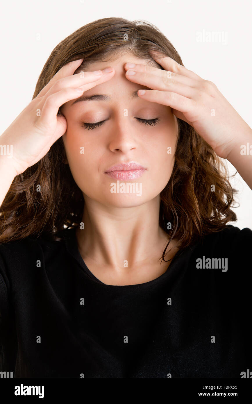 Woman suffering from an headache, holding her hand to the head - Stock Image