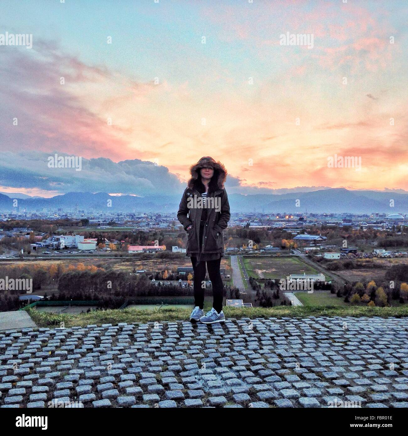 Full Length Of Woman In Hooded Jacket Standing Against Cityscape During Sunset - Stock Image