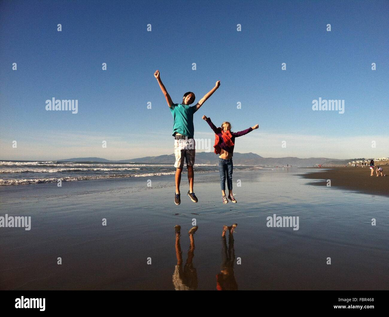 Full Length Of Brother And Sister Jumping At Beach - Stock Image
