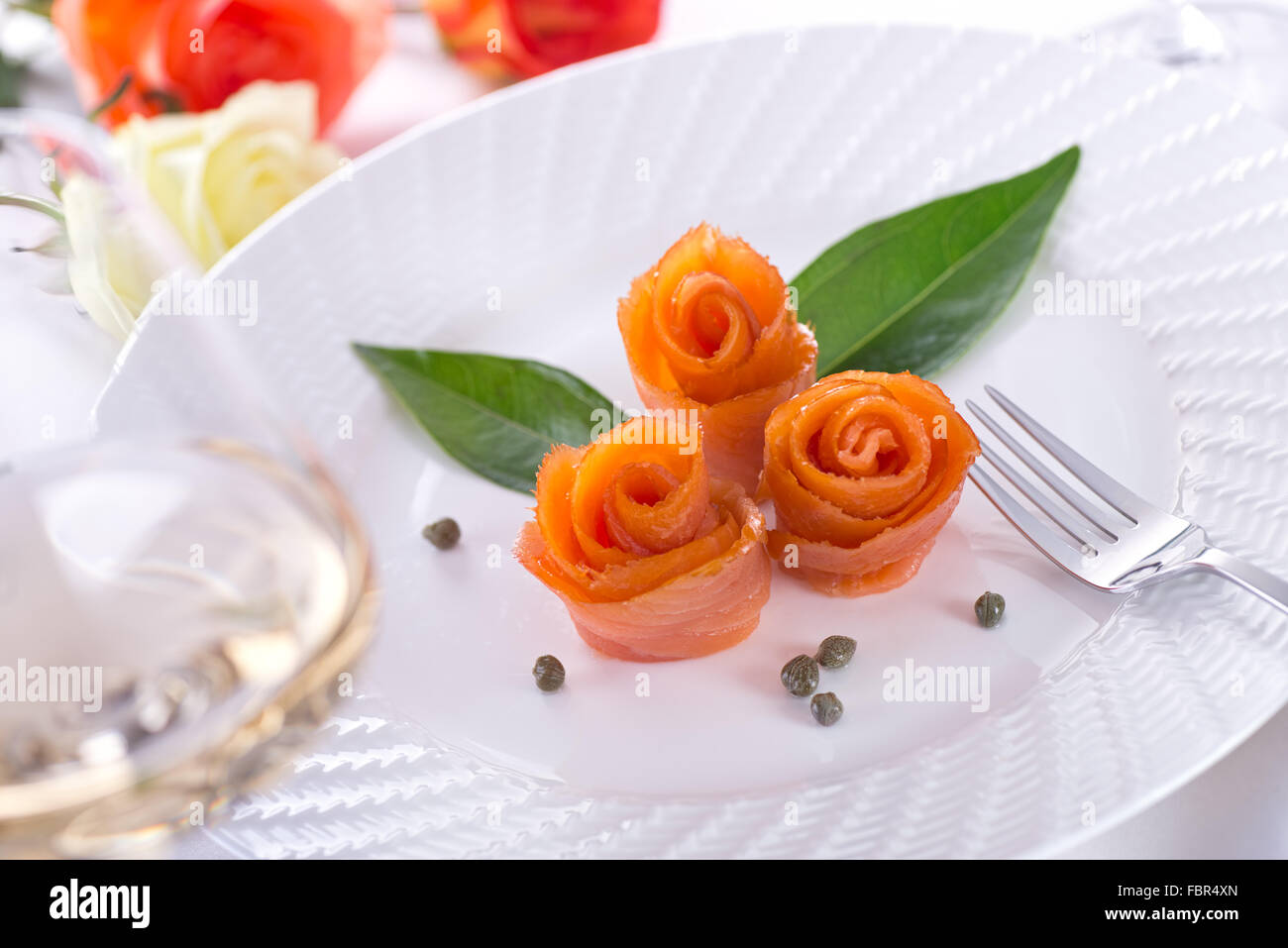 A group of delicious smoked salmon appetizers shaped like roses. - Stock Image