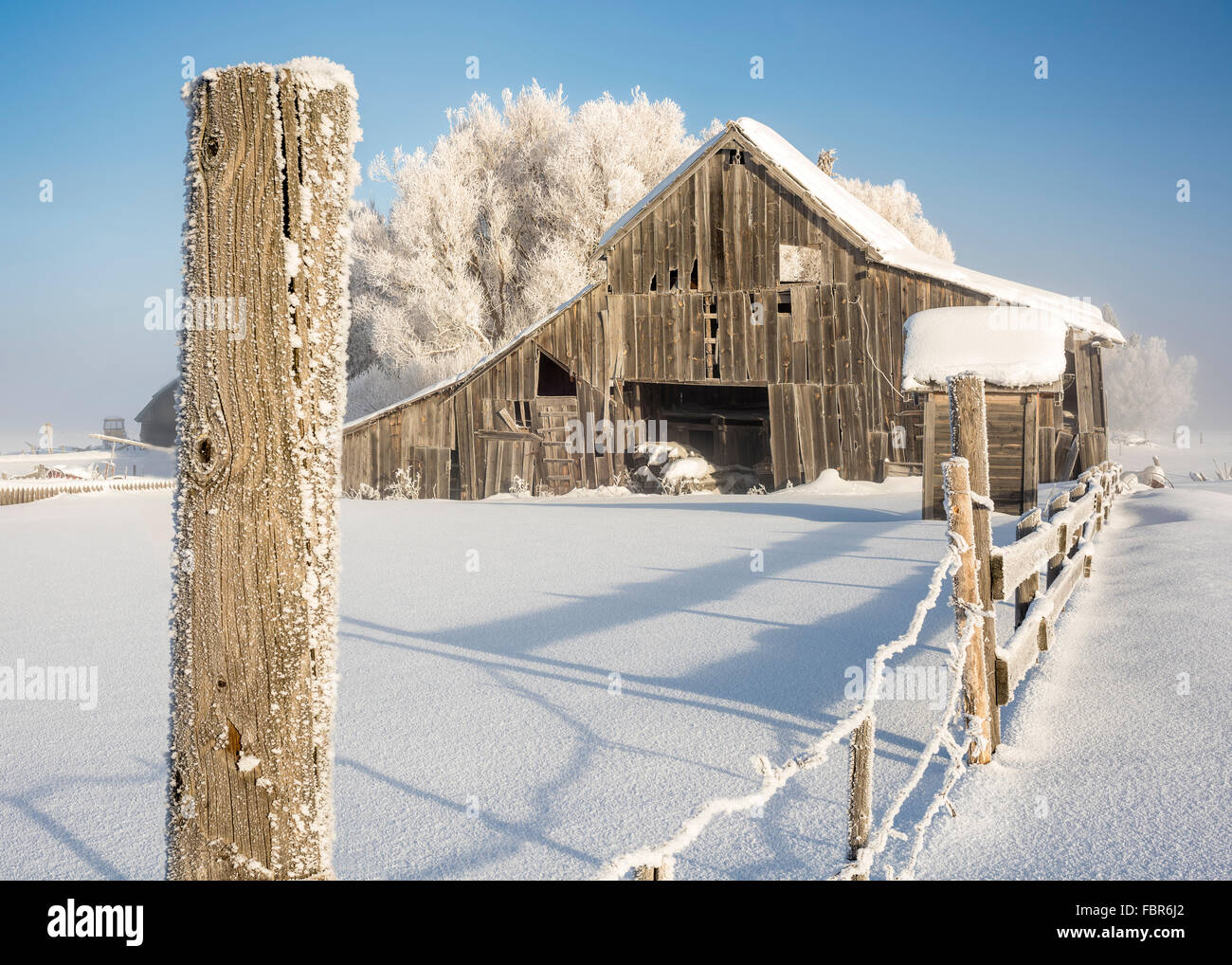 Classic Old Barn In Winter With A Fence Post Stock Photo