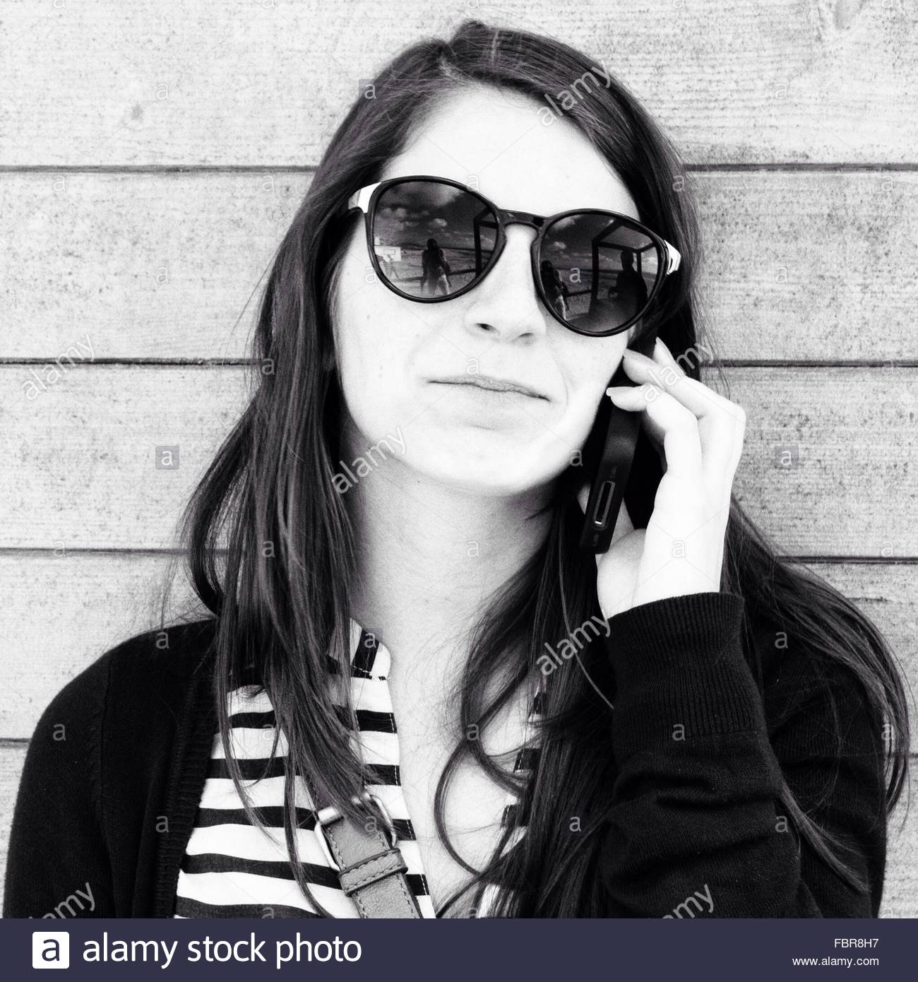 Portrait Of Young Woman Wearing Sunglasses While On Call Against Wooden Wall - Stock Image