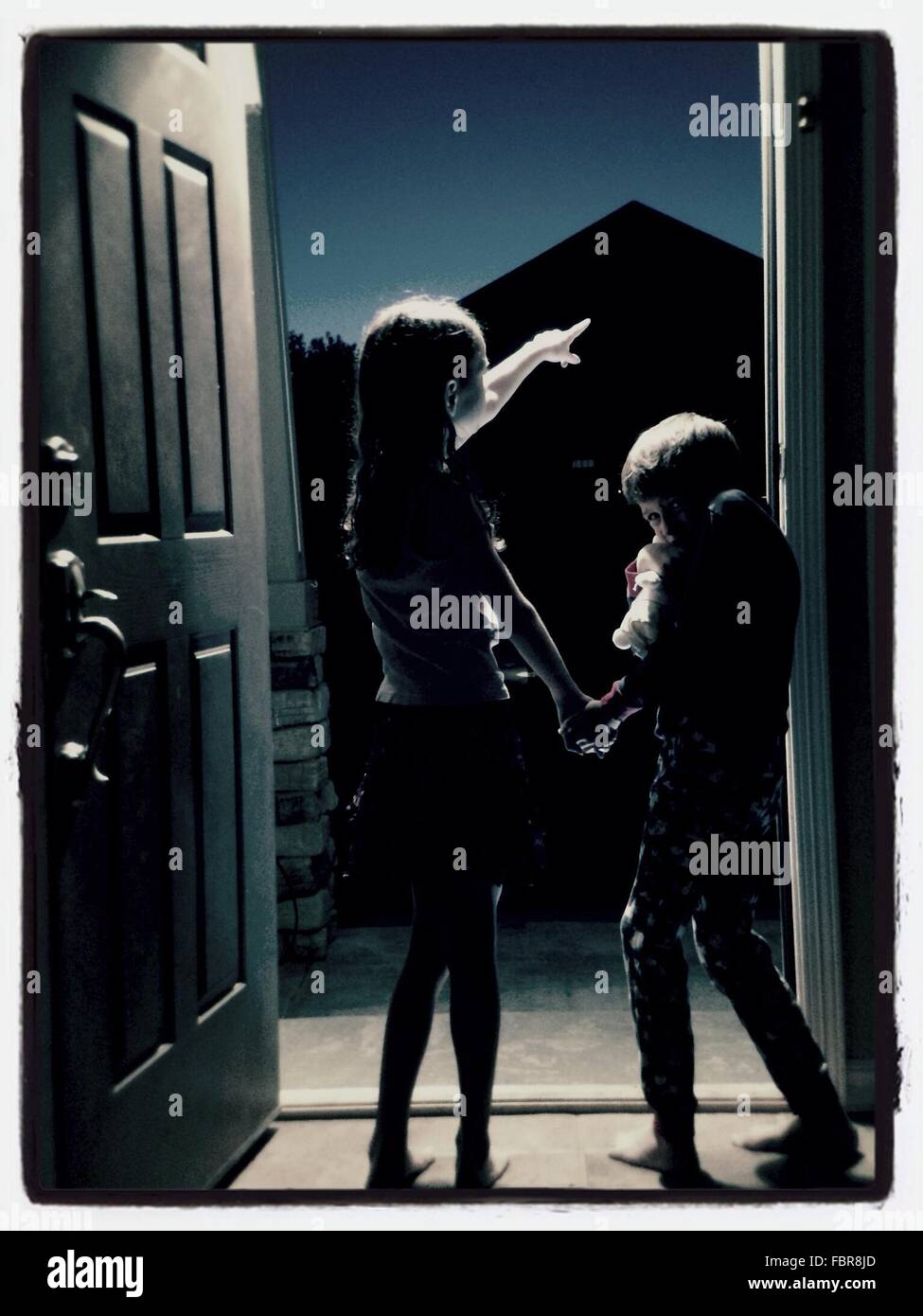 Siblings Standing On Door At Night - Stock Image