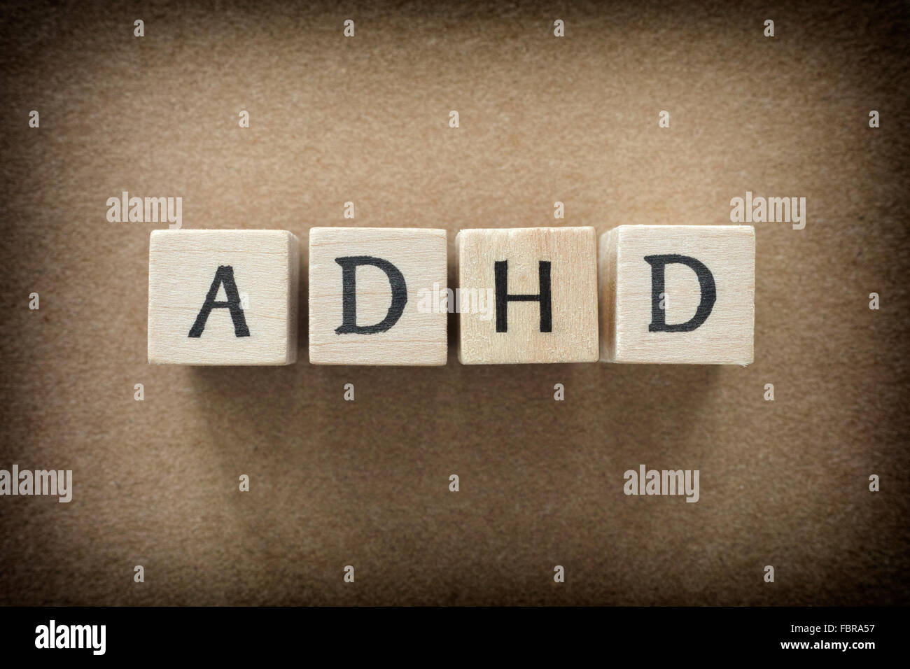 ADHD abbreviation on wooden blocks. ADHD is Attention deficit hyperactivity disorder. Close up. Vignette. - Stock Image