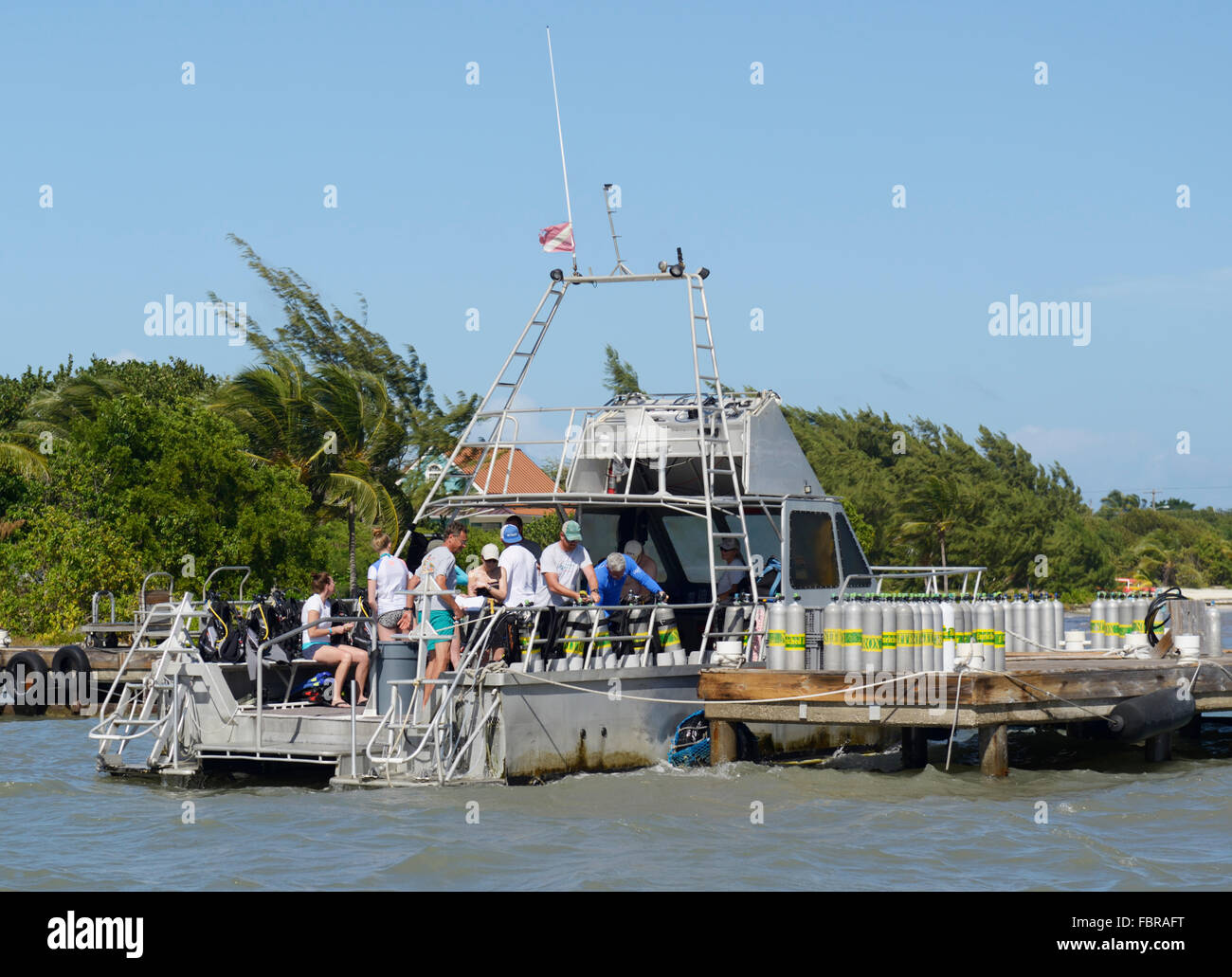 Dive boat with divers preparing to depart the dock and air tanks lined up on dock, Ocean frontiers, East End, Grand - Stock Image