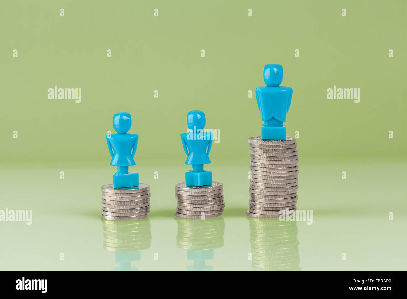 Male and female figurines standing on top of columns of coins. Wage gap concept illustration. - Stock Image