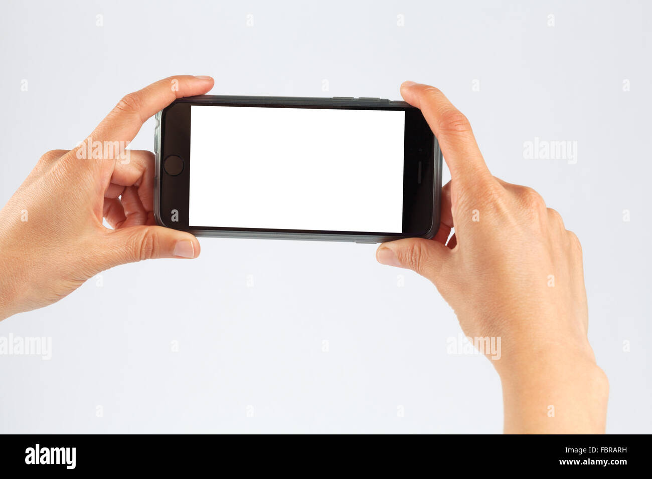 Female hands holding mobile phone in horizontal orientation. Isolated on white with white screen. - Stock Image