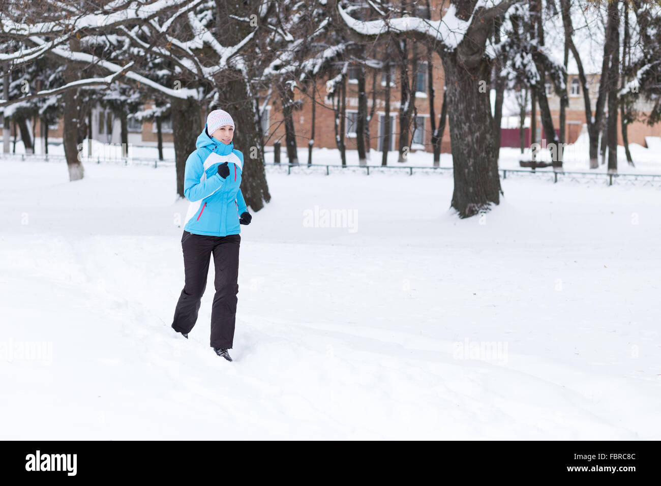 Young running or jogging caucasian woman in the winter park. - Stock Image