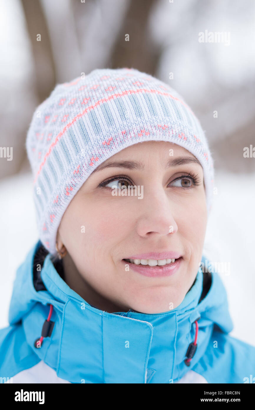 Close up portrait of young caucasian woman in sportswear. Smiling girl at the winter outdoors - Stock Image