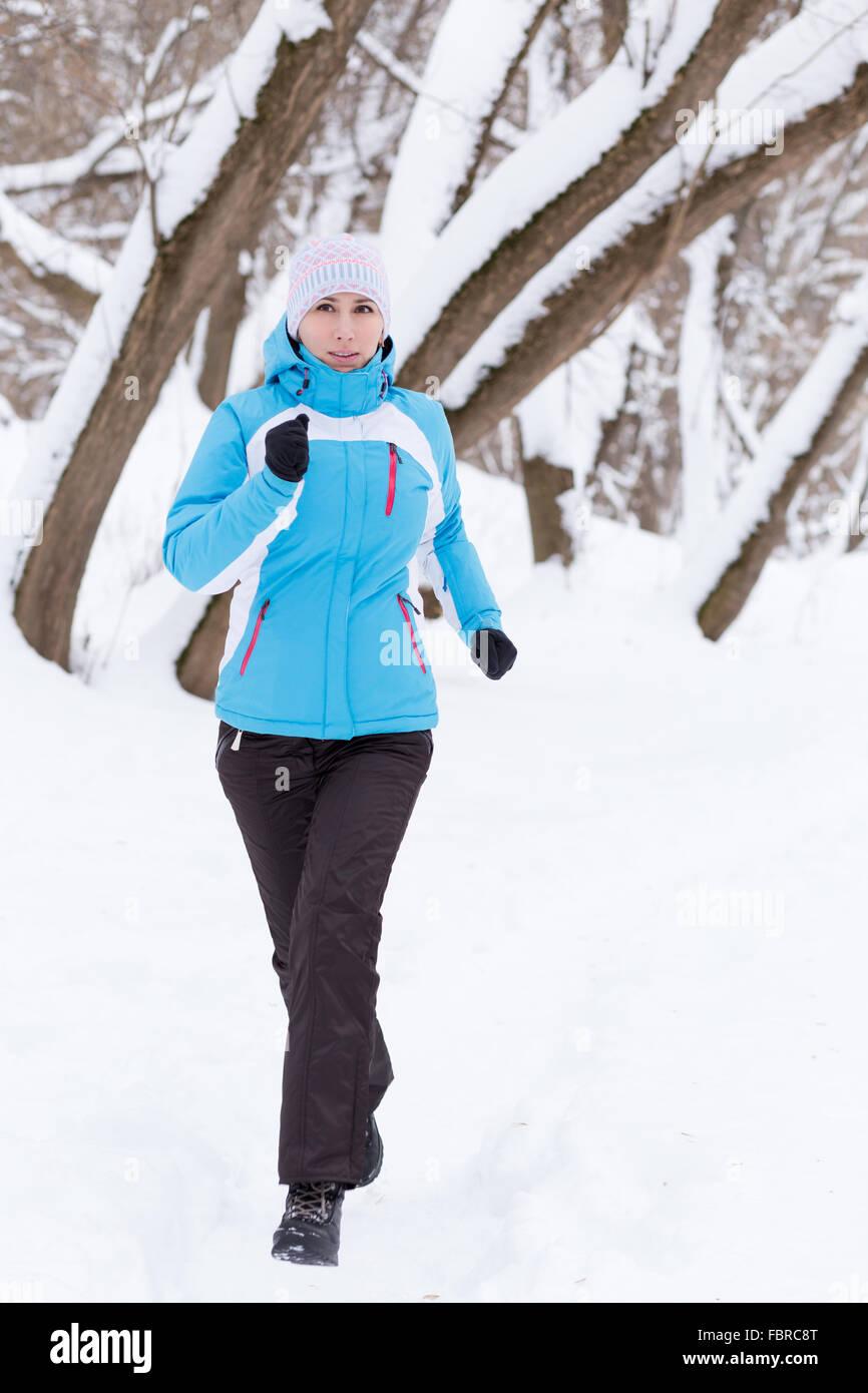 Young slim woman jogging in winter park. Running caucasian girl in sportswear - Stock Image