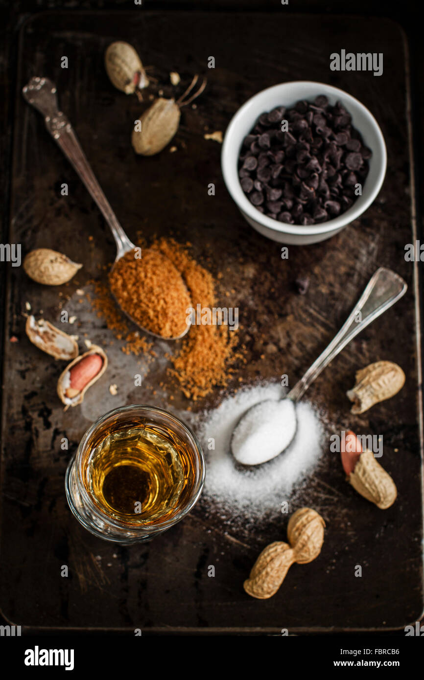 Work in progress for bourbon and peanut mini cakes: ingredients ready on a vintage pan - Stock Image