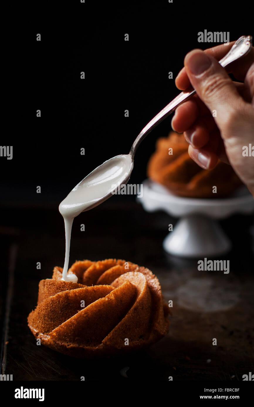 Work in progress for bourbon and peanut mini cakes: spreading boubon glaze over the top of a mini cake - Stock Image