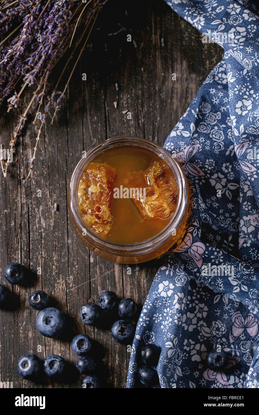 Open glass jar of liquid honey with honeycomb inside, fresh blueberries and bunch of dry lavender over old wooden - Stock Image