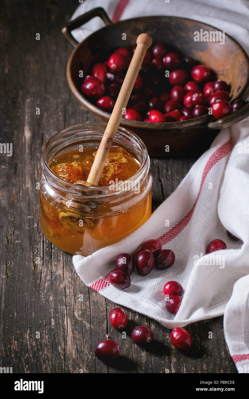 Open glass jar of liquid honey with honeycomb and honey dipper inside and fresh cranberries in vintage bowl over - Stock Image