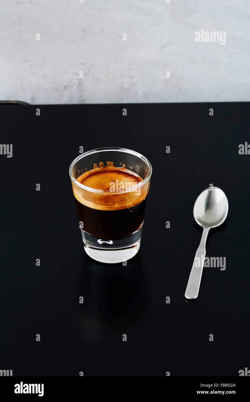Close-up of a shot of espresso on black metal table - Stock Image