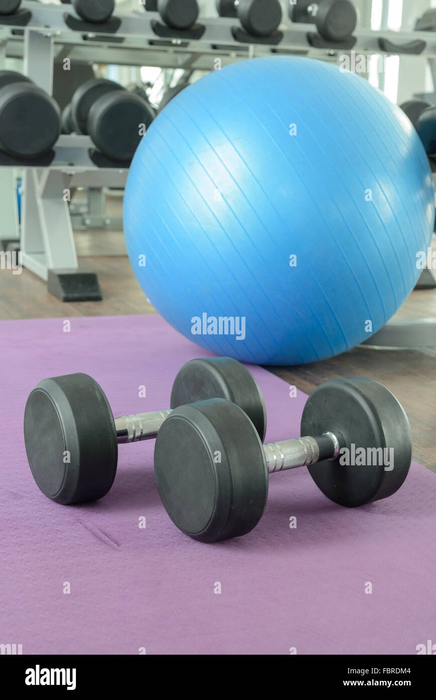 There are equipment for excercise in gym. (e.g. Rubber dumbbells, yoga ball, and yoga mat) Stock Photo