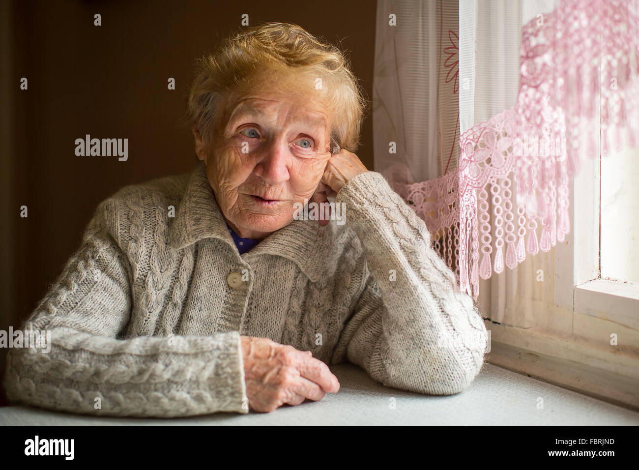 An elderly woman sits in the house near the window Stock ...