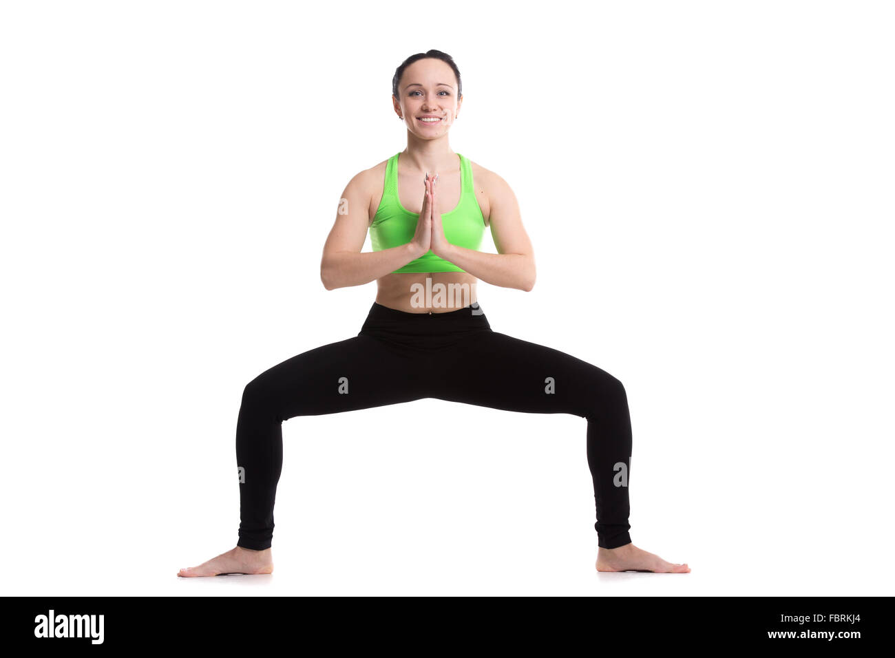 Slender fitness girl workout on white background, Goddess Pose (Utkata Konasana), temple or sumo pose, stupasana, - Stock Image