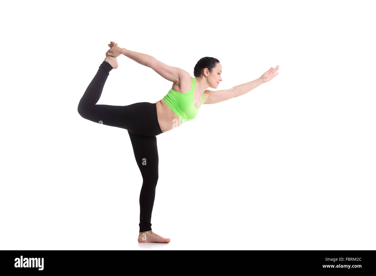 Beautiful sporty girl practices yoga, performing Natarajasana, Lord of the Dance pose, balance workout, full body - Stock Image