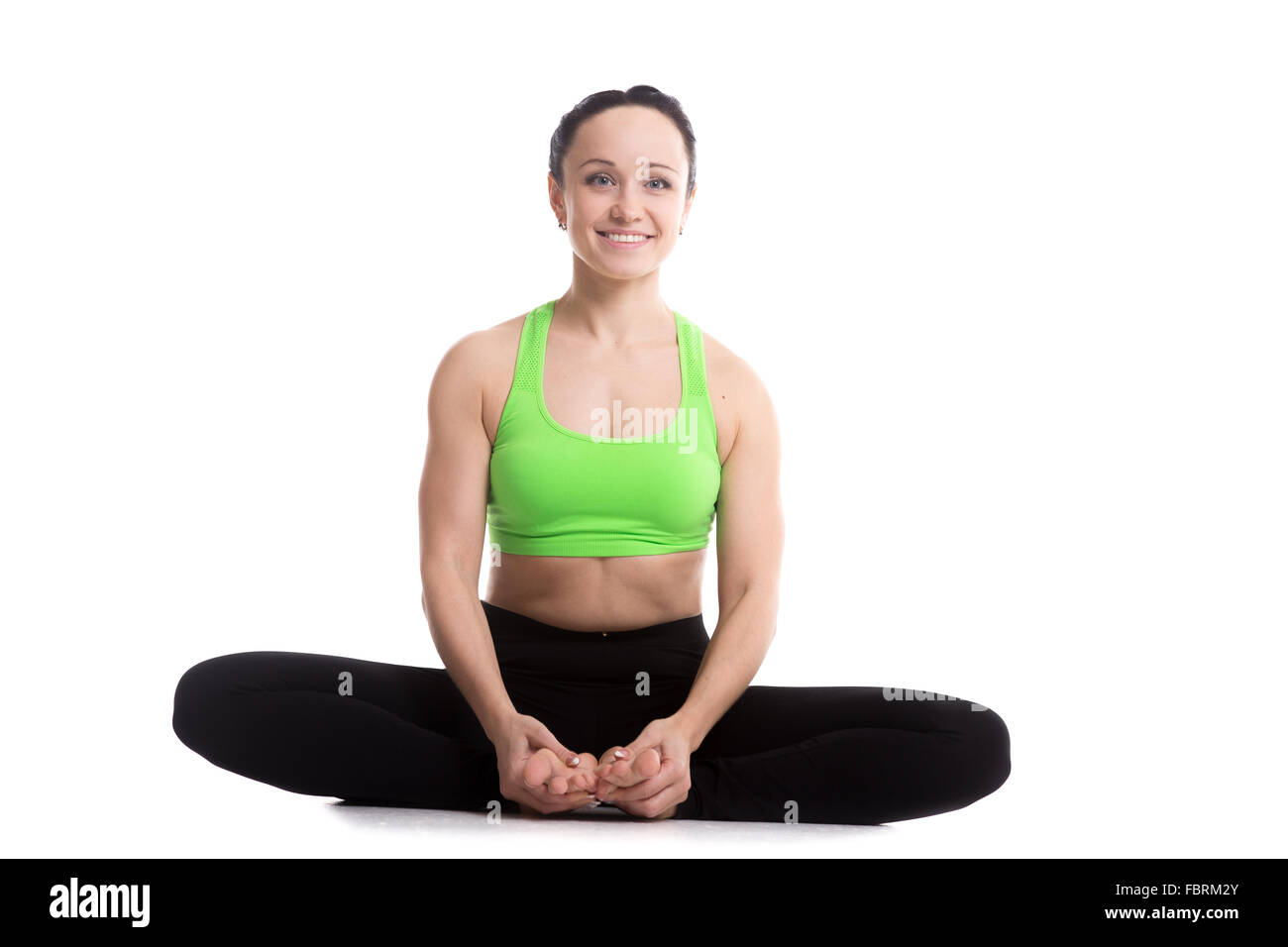 Happy smiling sporty girl doing yoga training, bound angle posture, baddha konasana, cobbler pose - Stock Image